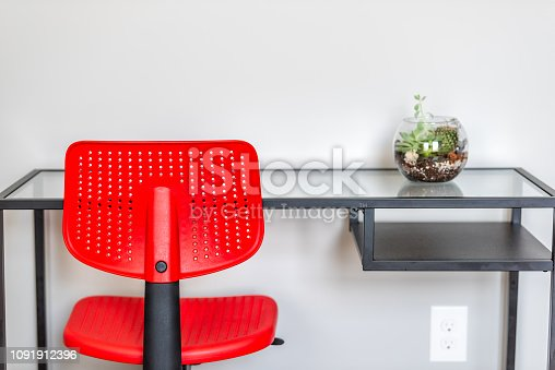 Green terrarium plant in small glass flowerpot on empty table in minimalism staged house interior and white wall bedroom office with red vibrant colorful desk chair and nobody