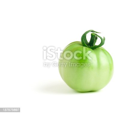 An unripe green tomato on a pure white background.