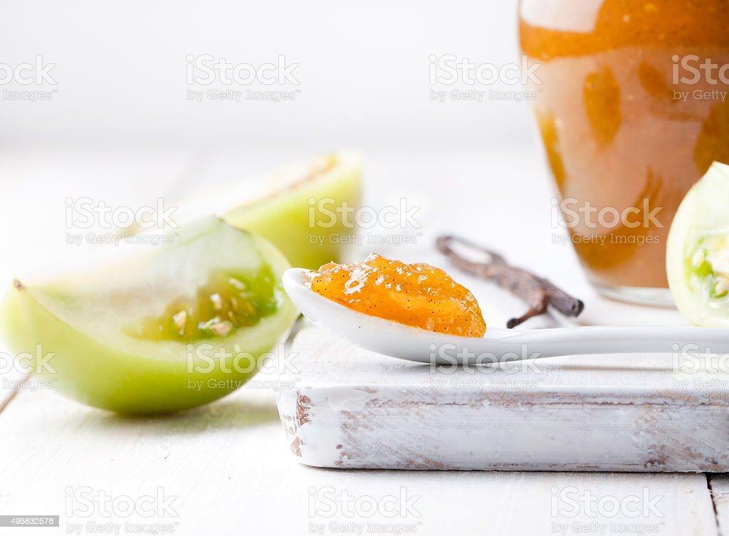 Green tomatoes jam with vanilla pods in a glass jar stock photo