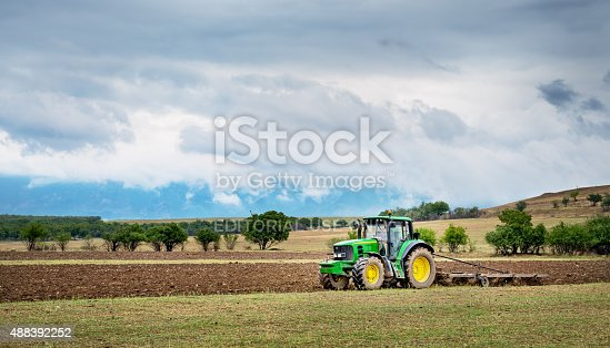 Karlovo, Bulgaria - August 22th, 2015: Ploughing a field with John Deere 6930 tractor. John Deere 8100 was manufactured in 1995-1999 and it has JD 7.6L or 8.1L 6-cyl diesel engine.