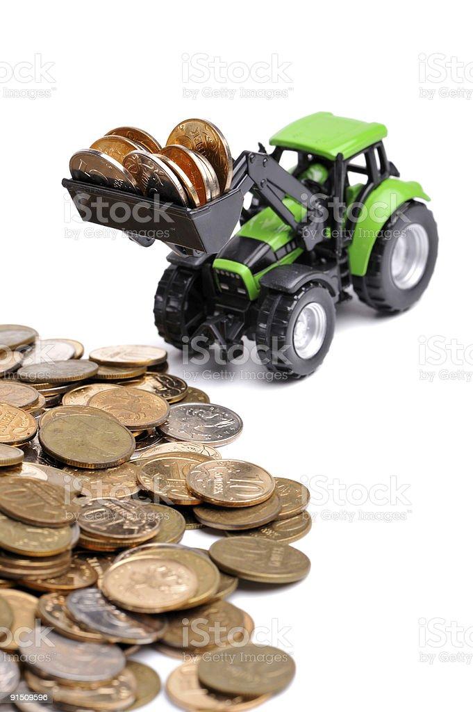 Green tractor raking up coins royalty-free stock photo