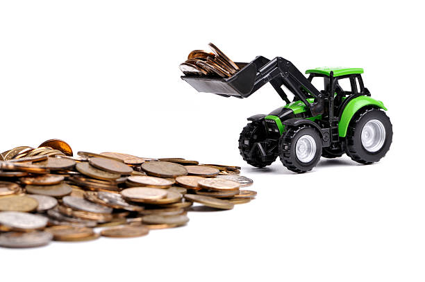 Green tractor raking up coins stock photo