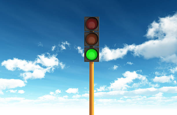 Green Traffic Light against Blue Sky Backgrounds stock photo