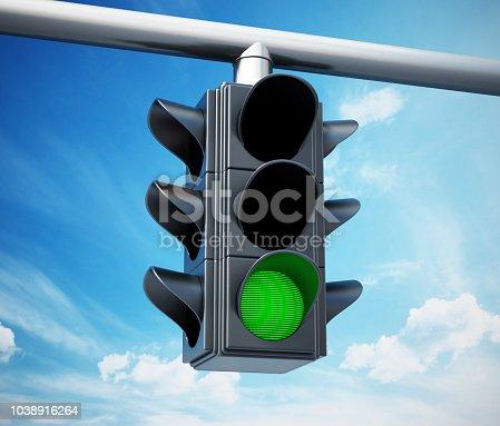 Green traffic light against blue sky
