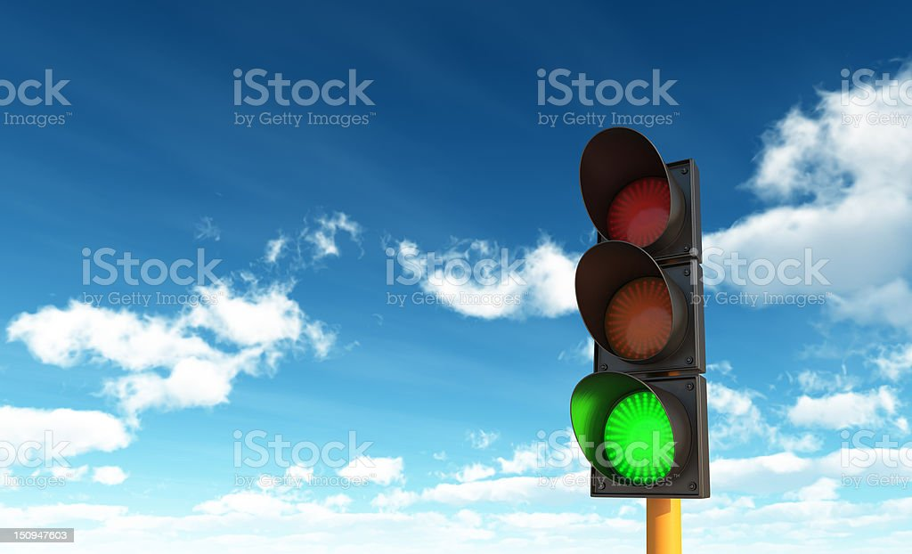 Green traffic light in front of a blue sky with clouds stock photo