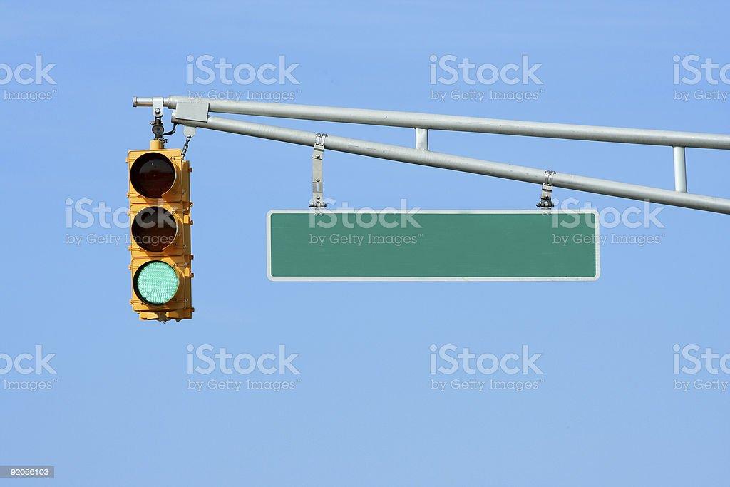 Green traffic signal light with sign stock photo