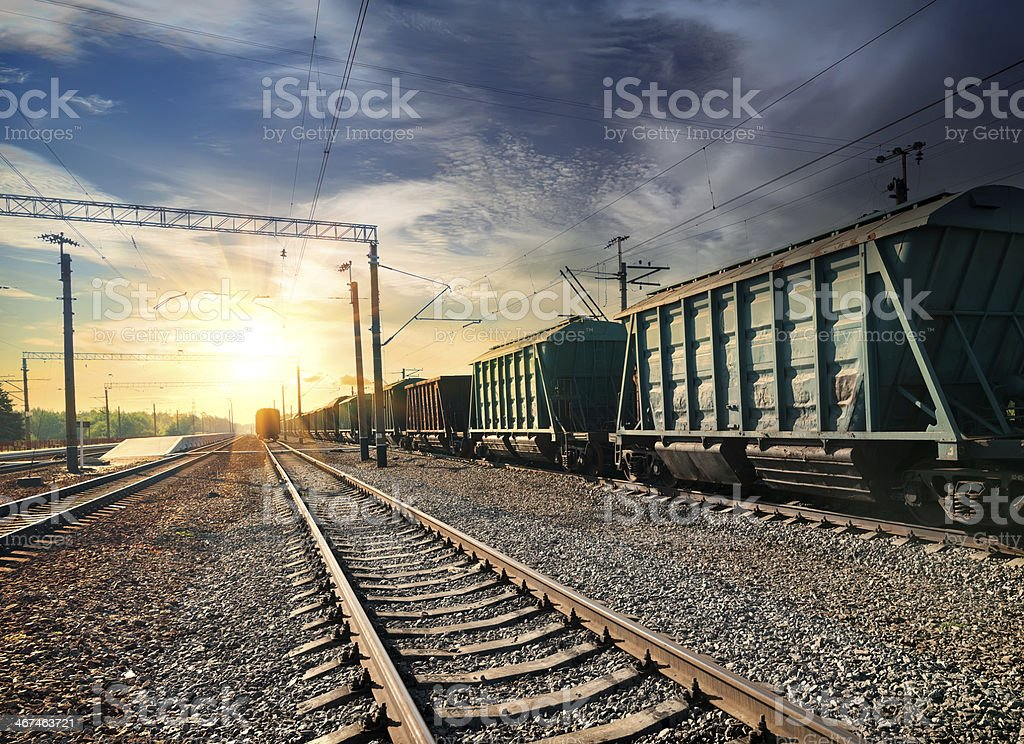 Green train and railroad tracks leading to dramatic sunset stock photo