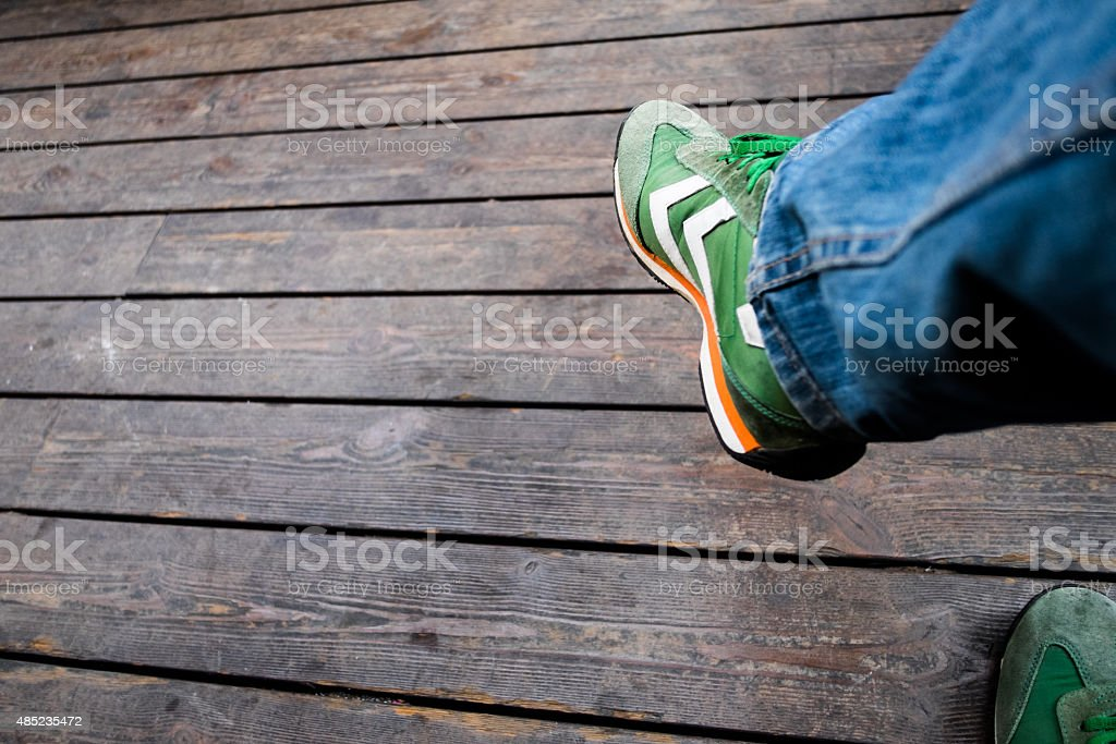 Green trainers and wooden background stock photo