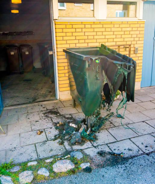 зеленый мусорный контейнер, расплавленный одной колючкой. - dumpster fire стоковые фото и изображения