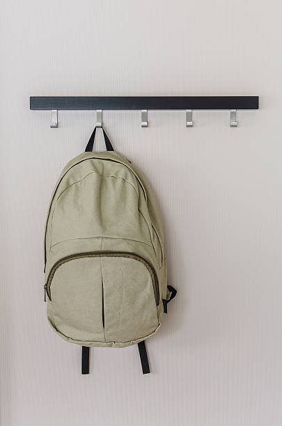 green travel backpack hanging on the wall stock photo