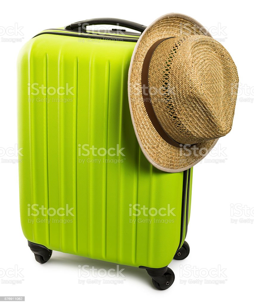 Green travel suitcase with straw hat isolated on white background stock photo