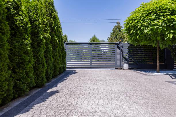 green trees and grey entry gate to the property during summer. real photo - portão imagens e fotografias de stock