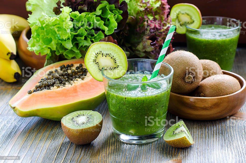 Green tropical smoothie with kiwi, papaya and salad leaves stock photo