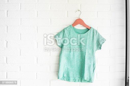Green tshirt hanging on an orange hanger