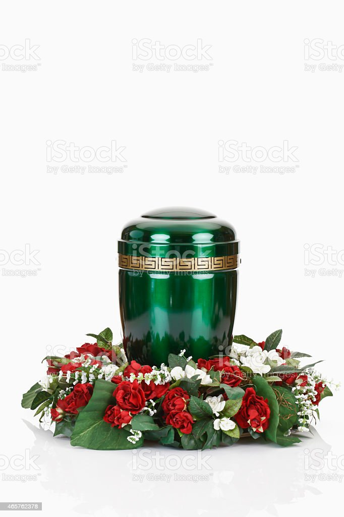 Green urn and floral wreath on white background stock photo