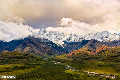 View over a green valley with colorful snowy mountains and a cloudy sky in the background in the Denali National Park and Preserve, Alaska. Alaskan Tundra forest and the Polychrome Mountains