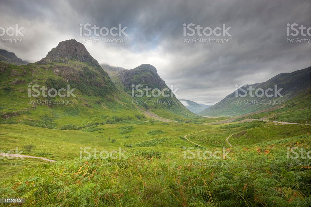 Green valley with a trail and a mountain view under gray sky royalty-free stock photo