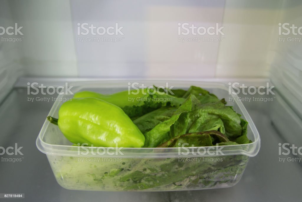 Green vegetable (salad and pepper) in the plastic food container on a shelf of a fridge. stock photo