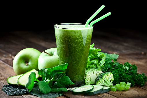 Glass of fresh green vegetable juice with two drinking straws on rustic wood table. The glass is surrounded by green vegetables like spinach, lettuce, broccoli, celery, green apples, parsley and cucumber. This is a drink used for detox diet. Predominant colors are green and brown.  DSRL studio photo taken with Canon EOS 5D Mk II and Canon EF 70-200mm f/2.8L IS II USM Telephoto Zoom Lens
