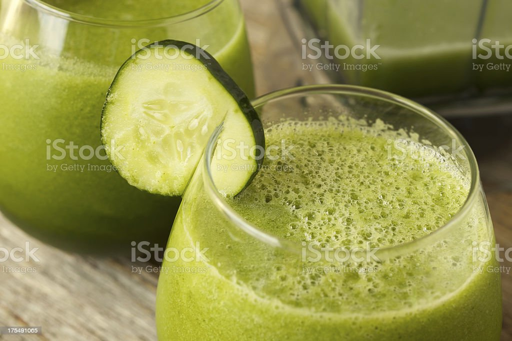 Green vegetable juice with cucumber garnish royalty-free stock photo