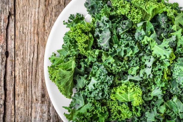 grünes gemüse, blätter von kohl, draufsicht, closeup auf weißen teller - gemüsechips stock-fotos und bilder