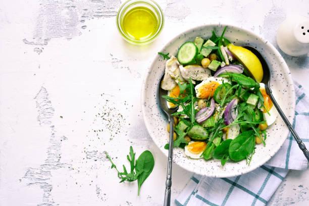 Grüner Salat mit Kichererbsen, Hähnchenfilet und gekochten Eiern – Foto