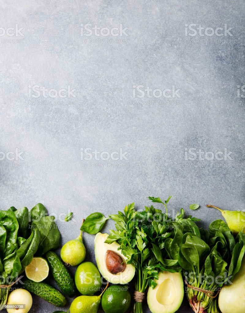 Green vegetables and herbs assortment on a grey stone background. Top view. Copy space stock photo