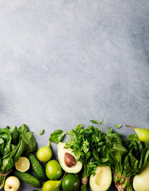 灰色の石背景に緑色野菜やハーブ品揃え。平面図です。コピー スペース - ローフード ストックフォトと画像