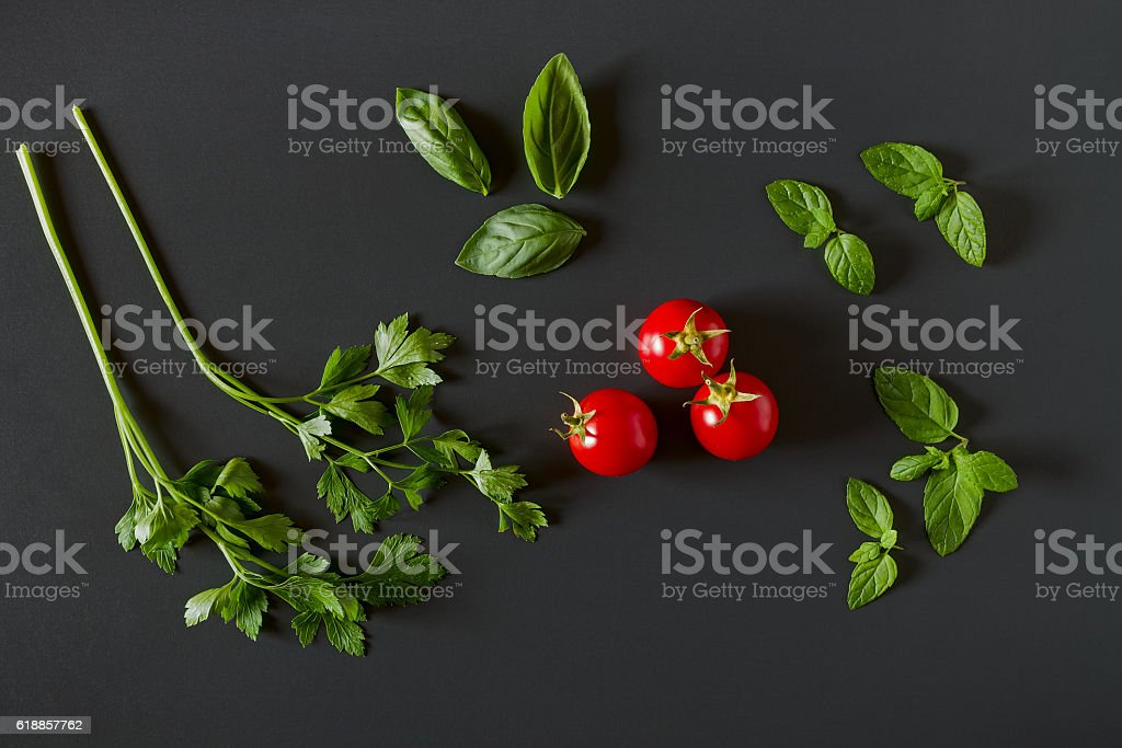 Green vegetables around three red tomatoes stock photo