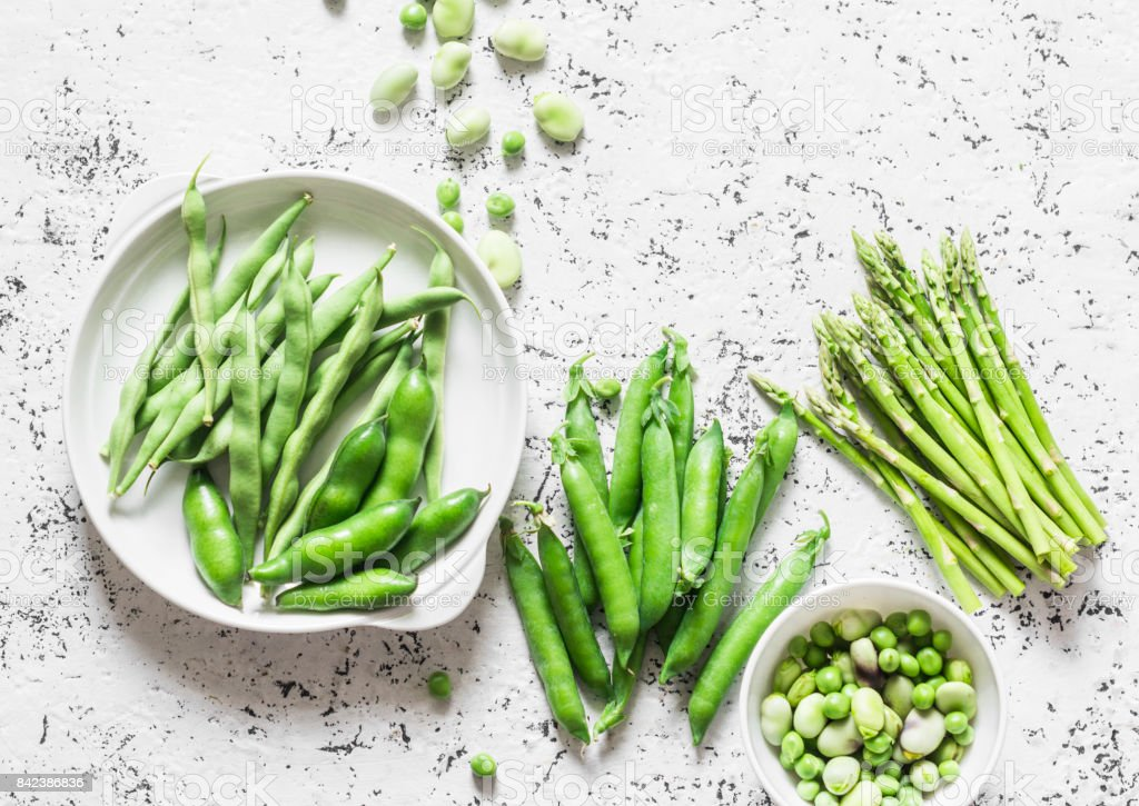 Green vegetables - asparagus, green beans and peas on a light background, top view stock photo