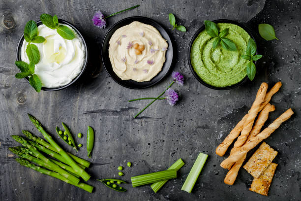 Green vegetables raw snack board with various dips. Yogurt sauce or labneh, hummus, herb hummus or pesto with crackers, grissini bread and fresh vegetables. Middle eastern meze snacks set stock photo