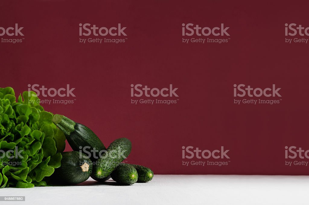 Green vegetables - salad spinach, cucumbers, zucchini on modern colorful bordo and white kitchen interior. Healthy vegeterian raw summer food ingredients. stock photo