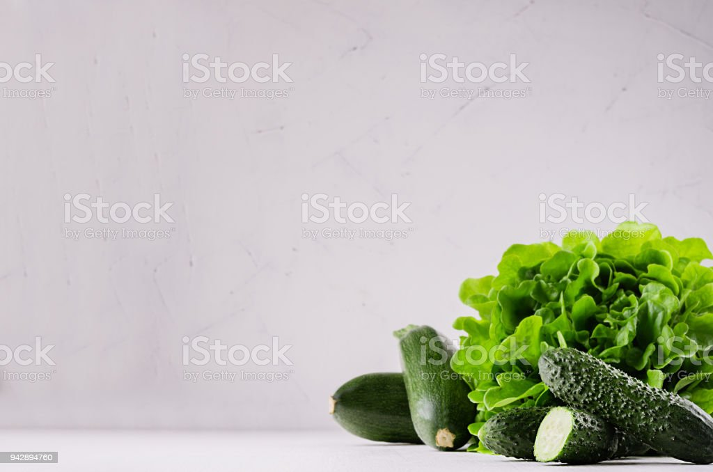 Green vegetables - salad spinach, cucumbers, zucchini on modern white kitchen interior. Healthy vegeterian raw summer food ingredients. stock photo