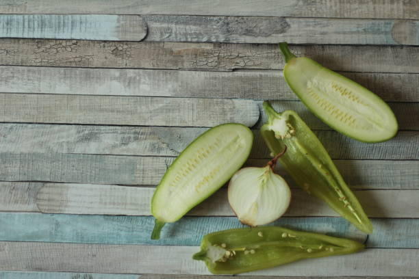 Green vegetables sliced in half on wooden table stock photo