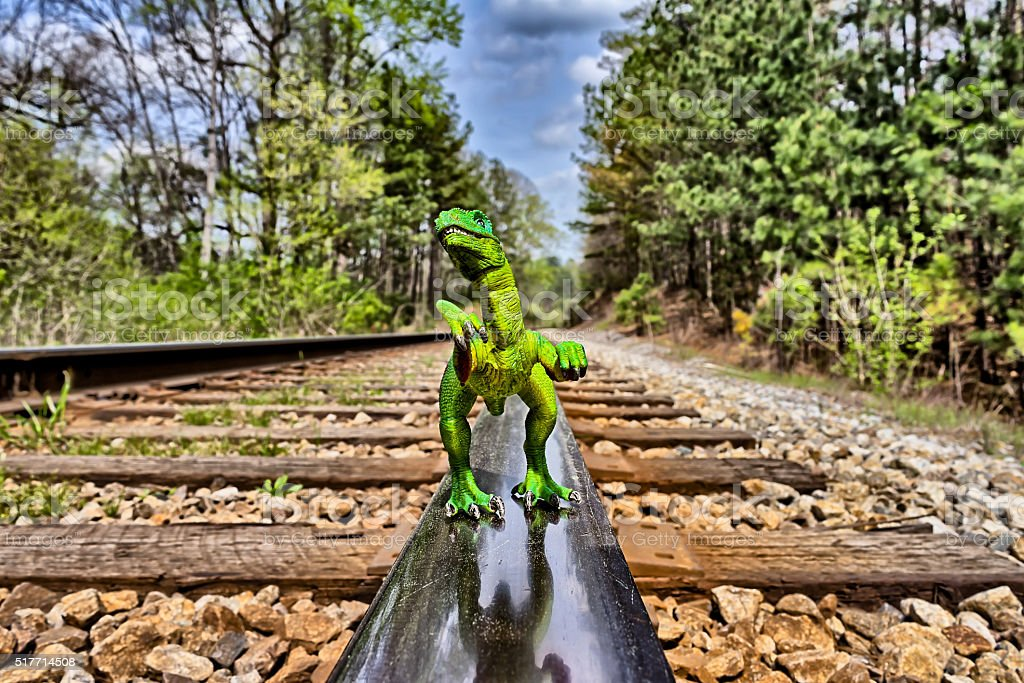 Green Velociraptor dinosaur walking on rail railroad tracks stock photo