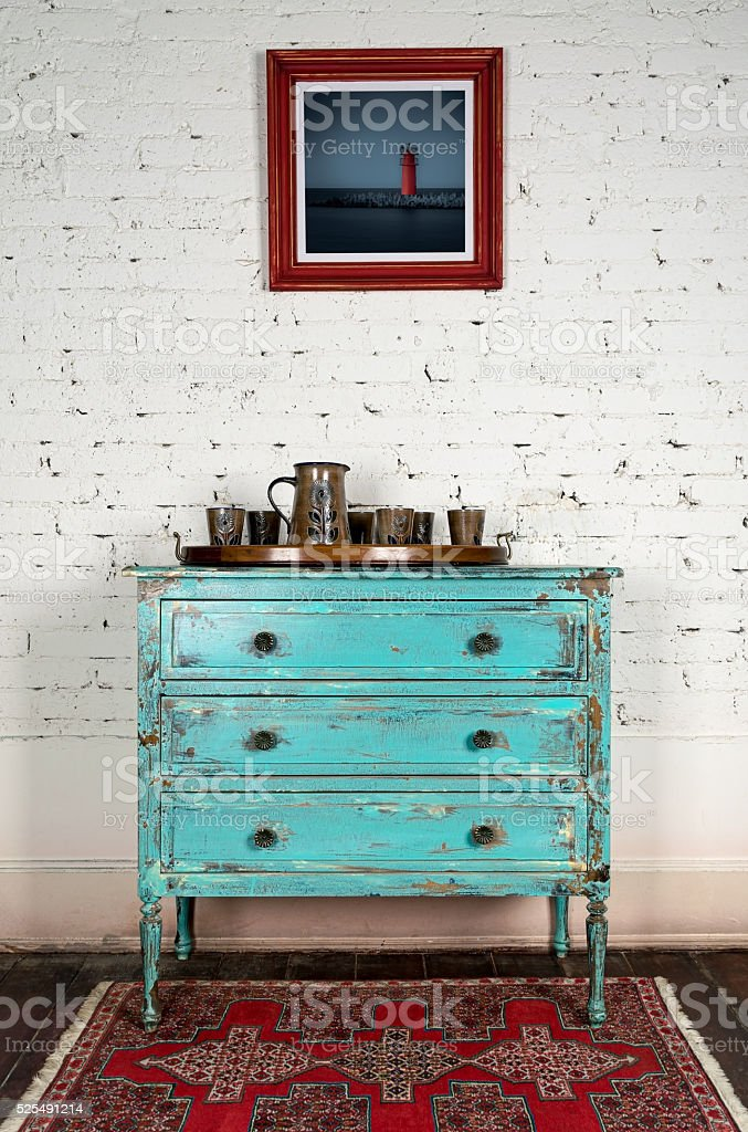 Green vintage cabinet and hanged painting on white bricks wall stock photo