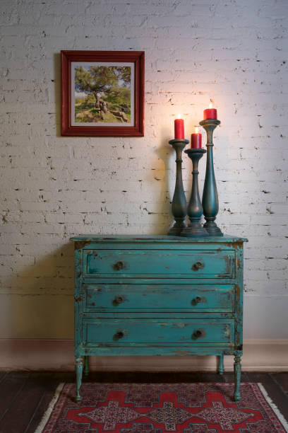 Green vintage cabinet, candlesticks and hanged painting on bricks wall stock photo