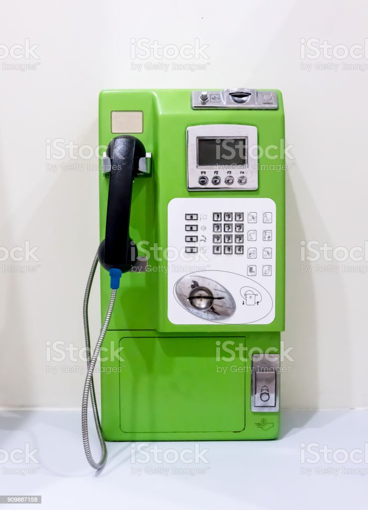 Green vintage public pay phone isolated on white background stock photo