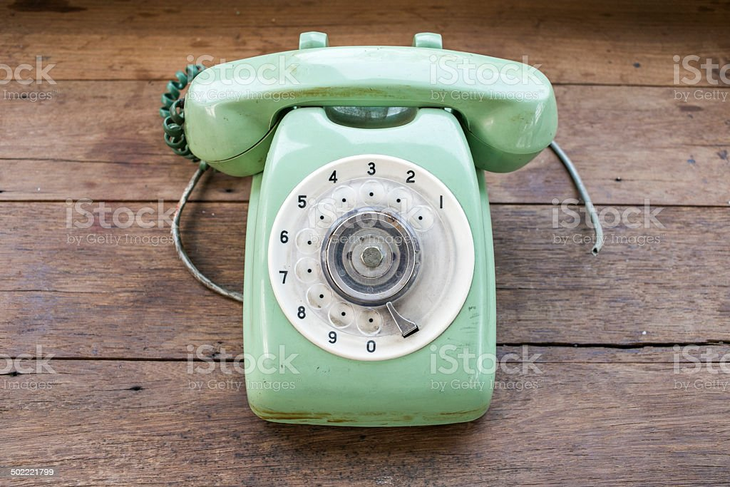 Green vintage telephone on brown wood desk background stock photo