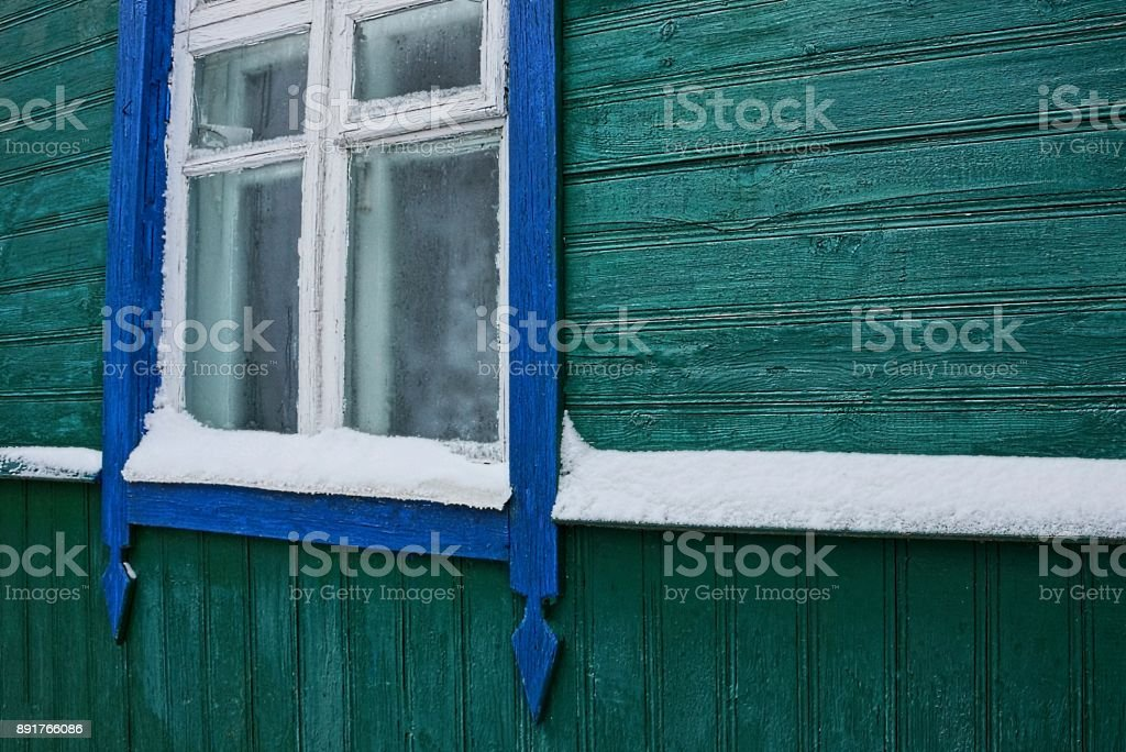 green wall of a wooden house with a window and white snow stock photo