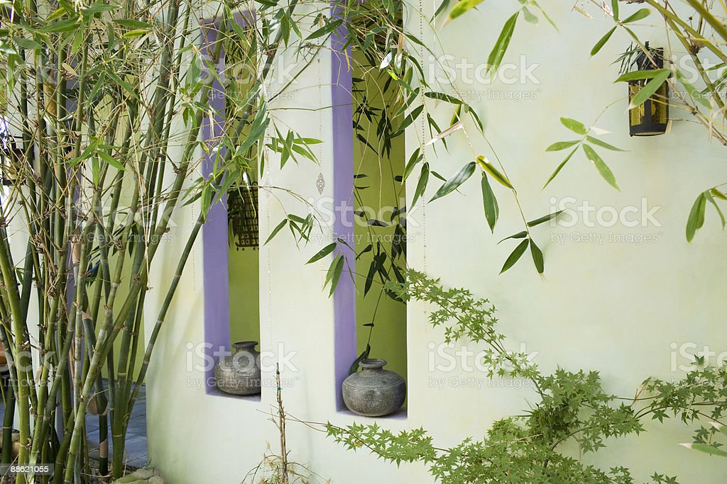 Green wall with bamboo and window openings royalty-free stock photo