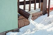 istock green wall with brown drainpipe in ice on a white snowdrift 1304262440