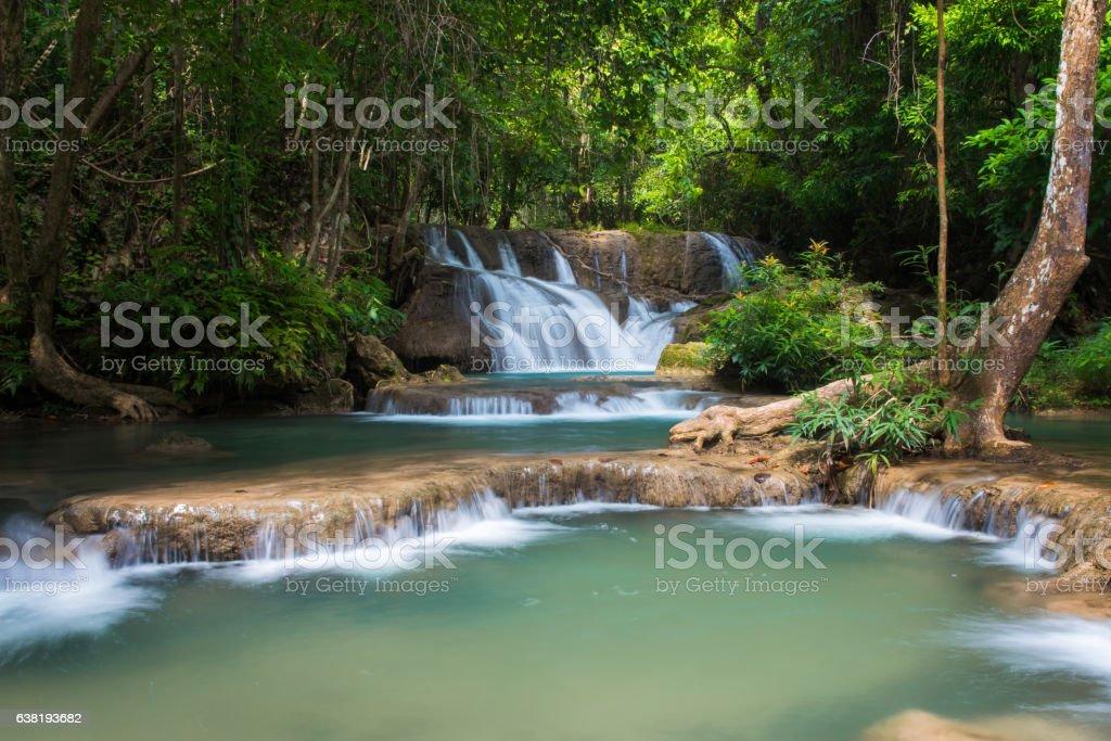 Green waterfall in deep forest, Erawan's waterfall stock photo