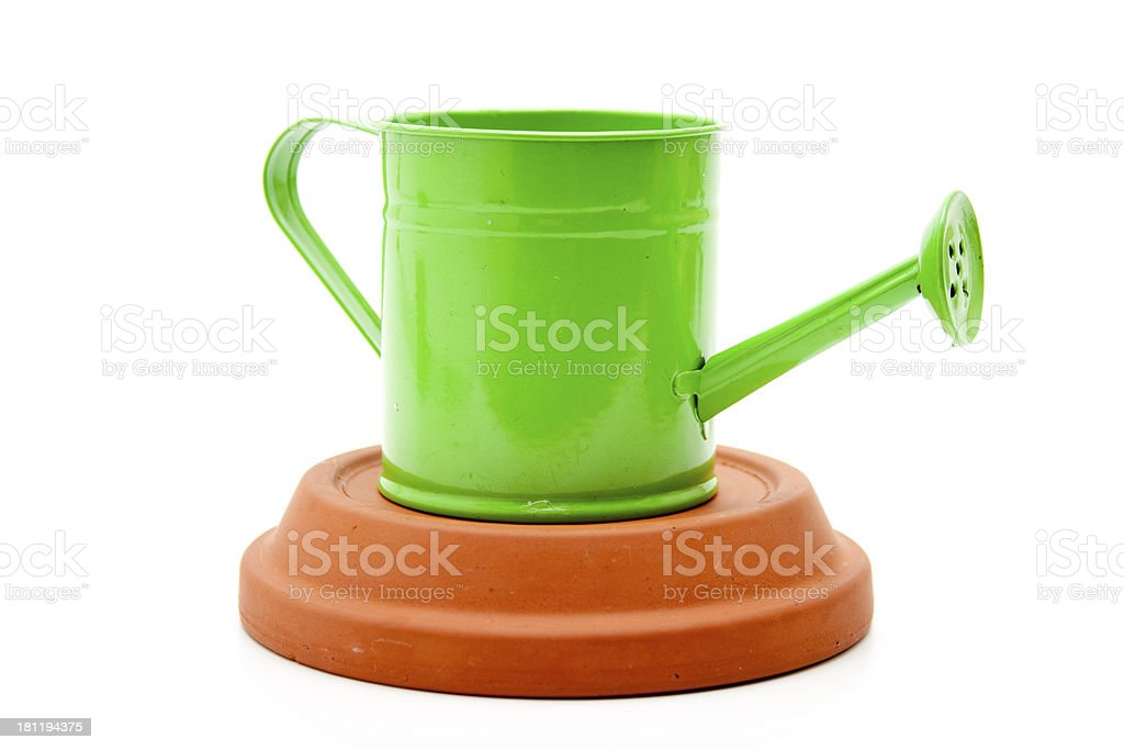 Green watering can on unterplate stock photo