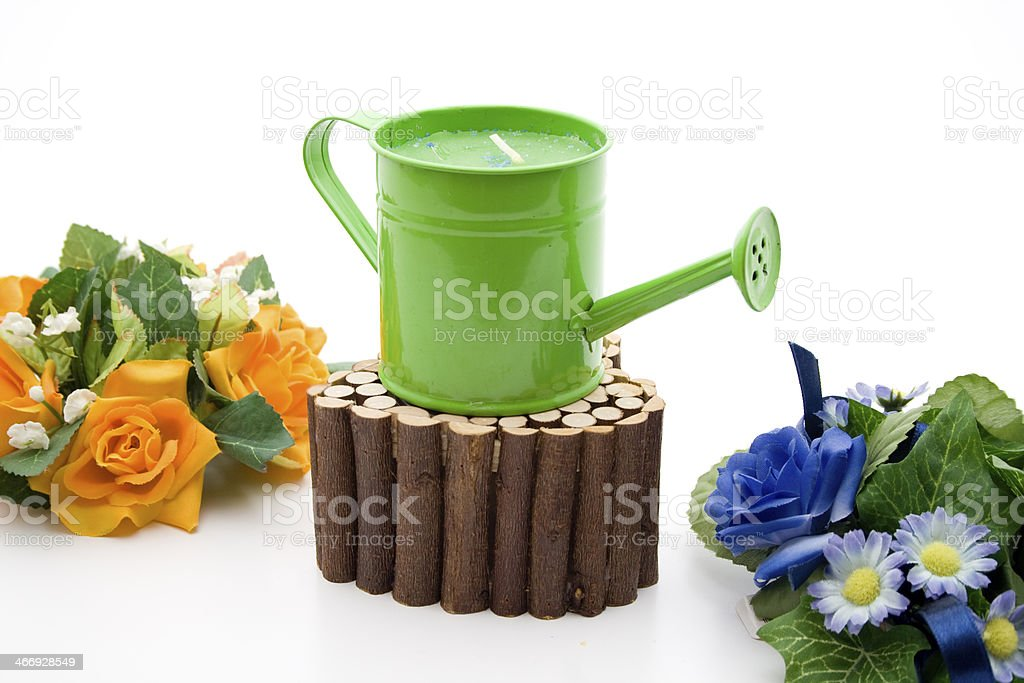 Green watering can on wooden stand and flowers stock photo