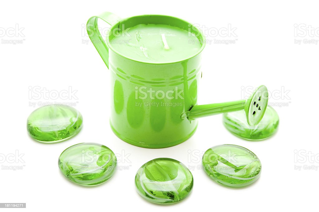 Green watering can with glass stones stock photo