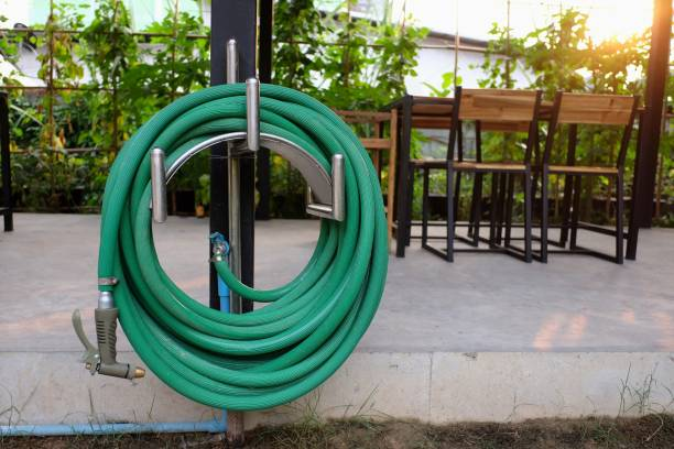 green watering hose in the garden - garden hose stock pictures, royalty-free photos & images