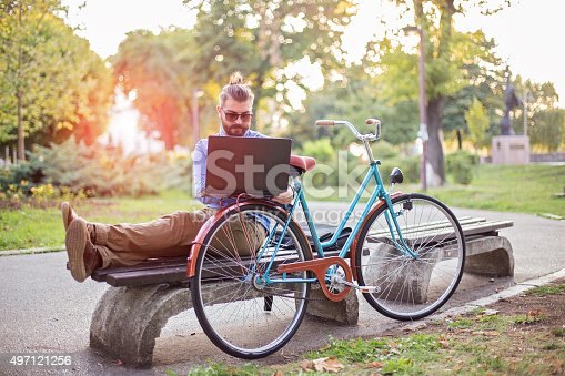 Young hipster businessman  using lap top ,sitting on  bench in the park,by his bike