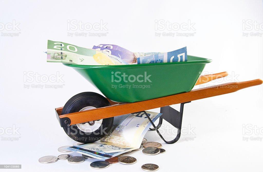 Green wheel barrel full of dollars bills royalty-free stock photo