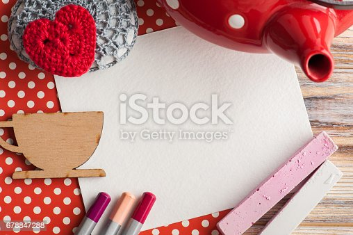 Red white polka dot desk with set of colorful pencils, blank note, chalk, teapot and wooden cup. Top view and copy space for text